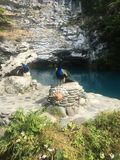 павлин у голубого озера в горах stock photo
