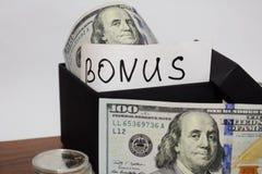 Пакет подарка с долларами на таблице на белой предпосылке, бонусе надписи стоковые фотографии rf