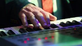 Пальцы более старого человека который играет электронный синтезатор сток-видео