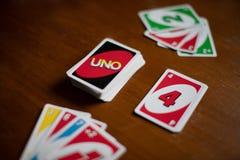 Палуба карт игры Uno разбросанных повсюду на таблицу Американская карточная игра стоковое изображение