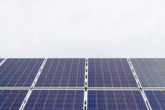 Панели фотоэлемента фотовольтайческие на заводе производства энергии с голубым облачным небом на заднем плане стоковое фото