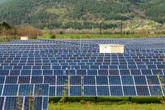 Панели солнечных батарей, photovoltaics, альтернативный источник электричества Взгляд солнечной станции на предгорьях горы - конц стоковая фотография