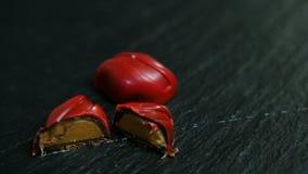 Панорама на целом и отрезок в половинных небольших красных конфетах шоколада видеоматериал