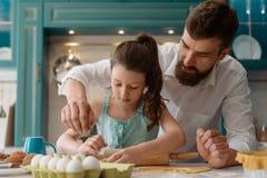 Папа помогает дочери с варить стоковое фото rf