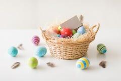 Пасхальные яйца и поздравительная открытка в корзине стоковое изображение