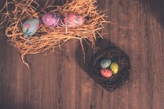 Пасхальные яйца на кровати и гнезде соломы стоковые фотографии rf