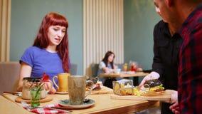 Пара сидя таблицей в кафе выпивая чай Официант приносит заказ видеоматериал
