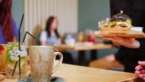 Пара сидя таблицей в кафе и официанте приносит заказ видеоматериал