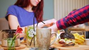Пара сидя таблицей в кафе и официанте приносит заказ 2 черных бургера сток-видео