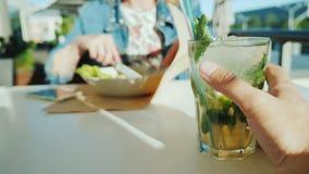 Пара отдыхает в кафе Первый взгляд человека - человек держа стекло с коктейлем, женщиной на заднем плане видеоматериал