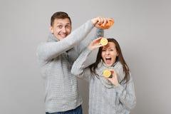 Парень девушки пар потехи в серых свитерах, шарфах совместно держит оранжевый лимон изолированный на серой студии предпосылки сте стоковое фото rf