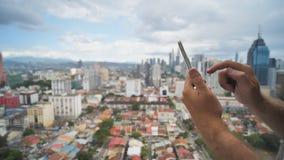 Парень работает со смартфоном на запачканной предпосылке Куала Лумпур Руки и поднимающее вверх телефона близкое Малайзия сток-видео
