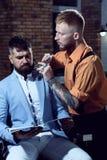 Парикмахер брея бородатого человека в парикмахерской Парикмахер человека бороды посещая в парикмахерскае парикмахерскаь sandalwoo стоковое изображение rf