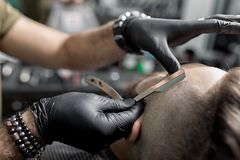 Парикмахер в черных перчатках уравновешивает висок зверского бородатого молодого человека с прямой бритвой на парикмахерскае стоковое фото rf