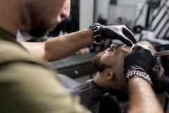 Парикмахер в черных перчатках уравновешивает висок зверского бородатого молодого человека с прямой бритвой на парикмахерскае стоковые фотографии rf