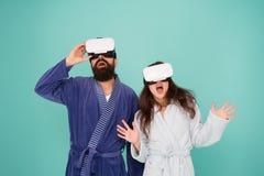 Пары в купальных халатах носят стекла vr Сознательный будить Возвращение в реальность Человек и женщина исследуют vr Технология V стоковое фото rf