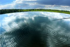 пейзаж. Fishing on a beautiful lake near the dense forest stock photo
