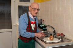 Пенсионер варя его обедающий стоковые фотографии rf
