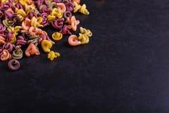Пестротканые макаронные изделия с дополнением естественной краски овоща Разбросанный на черную конкретную таблицу Взгляд сверху,  стоковое изображение