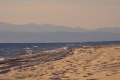 Песчаный пляж протягивая прочь в расстояние и силуэт гор на горизонте в светлом тумане никто стоковая фотография rf
