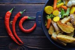 Печеные картофели с овощами в перце сковороды и chili стоковые изображения