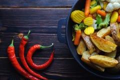 Печеные картофели с овощами в перце сковороды и chili стоковое фото rf