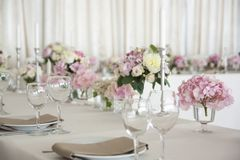 Перевести вGoogleBingFlower arrangements are on the table covered with a white tablecloth. Silver candlesticks. Flower stock images