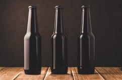 Пивные бутылки на деревянном столе/пивных бутылках на деревянном столе против темной предпосылки стоковая фотография rf