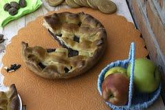 Пирог, кусок яблочного пирога с вишней и грецкими орехами, чашка чаю, яблоки в корзине, грецкие орехи и печенья на таблице стоковое фото rf