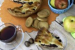 Пирог, кусок яблочного пирога с вишней и грецкими орехами, чашка чаю, яблоки в корзине, грецкие орехи и печенья на таблице стоковое фото