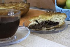 Пирог, кусок яблочного пирога с вишнями и грецкими орехами, чашка чаю и яблоки в корзине на таблице стоковое фото rf