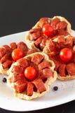 Пирог печенья слойки мини с томатом сосиски и вишни на плите деревянное предпосылки темное стоковые изображения