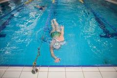 Плавание женщины в бассейне во время конкуренции стоковые фотографии rf