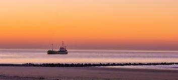 Плавание освещенного корабля в море на заходе солнца, бельгийском побережье, природе и предпосылке перехода стоковая фотография