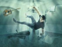 Плавать человека подводный в комнате имея мечту стоковое изображение rf