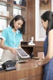 Планшет показа женщины к милому клиенту салона спа стоковая фотография rf