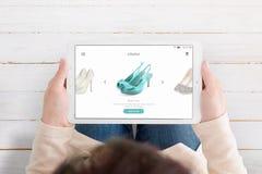 Планшет удерживания женщины и приложение ecommerce пользы для обнаружения новых ботинок стоковое фото rf