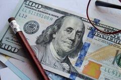 План дела Американские деньги, 100 долларов владение домашнего ключа принципиальной схемы дела золотистое достигая небо к стоковые фото