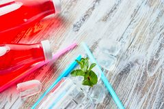 Пластиковые бутылки с ягодами, освежающим напитком разбросанные кубы льда и выпивая соломы на предпосылке затрапезное деревянного стоковые изображения