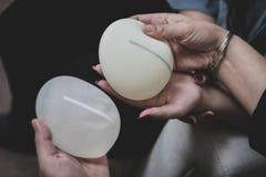 Пластический хирург и пациент обсуждают выбор грудных имплантатов после mastectomy или для увеличения груди стоковые изображения