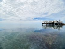 Платформа на поддержках в море около берега Низкая плотная облачность над морем стоковое фото