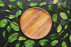 Плита положенная квартирой пустая деревянная и свежие листья шпината на темной предпосылке Взгляд сверху стоковое изображение rf