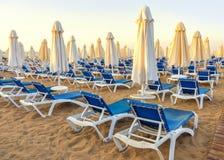 пляж к морю с шезлонгами и сложенными зонтиками, Турцией, бортовым курортом стоковые фото