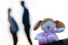 Плюшевый мишка на переднем плане и беременная женщина с человеком в предпосылке стоковая фотография rf