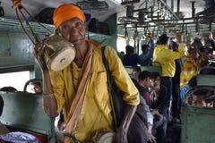Плохой попрошайка поя и умоляя на пригородном поезде стоковые фотографии rf