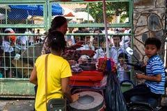 Пномпень, Камбоджа - 8-ое декабря 2018 Поставщик мороженого продавая к ребятам школьного возраста стоковое фото rf