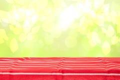 Пустая деревянная таблица палубы с красной striped скатертью над светом конспекта чувствительным ярким - желтые весна или предпос стоковая фотография rf