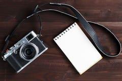Пустая страница блокнота и современная камера в классическом стиле на темном коричневом деревянном столе стоковая фотография rf