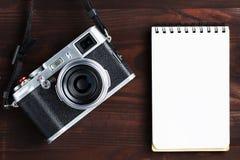 Пустая страница блокнота и современная камера в классическом стиле на темном коричневом деревянном столе стоковые изображения rf