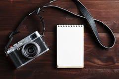 Пустая страница блокнота и современная камера в классическом стиле на темном коричневом деревянном столе стоковые изображения